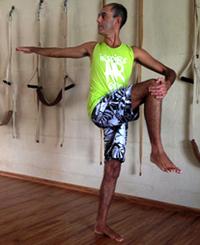 Cristiano em variação de parivrtta hasta padangusthasana, uma postura de equilíbrio com torção, na sala de Yoga do Ar+Zen. Foto por Ana Lorena Magalhães