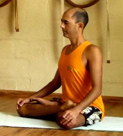 Cristiano meditando em padmasana, a postura da flor de lótus, na sala de Yoga do Ar+Zen