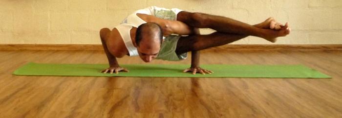 Cristiano em ashtavakrasana, uma postura de torção com equilíbrio sobre as mãos, na sala de Yoga do Ar+Zen » foto por Marília Romano