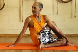 Cristiano em matsyendrasana, uma postura clássica de torção, na sala de Yoga do Ar+Zen