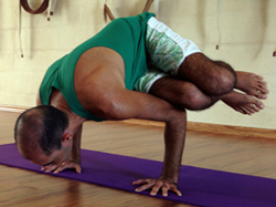 Cristiano em parshvabakasana, a postura lateral do corvo, na sala de Yoga do Ar+Zen. Foto por Raphaella Quintela