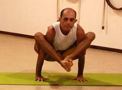 Cristiano Bezerra em bhujapidasana, a postura da pressão sobre os braços, na sala de Yoga do Espaço Núcleo Sol. Foto por Paola Marques.